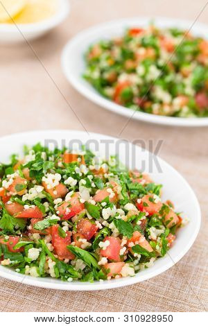 Fresh Vegan Tabbouleh Salad Made Of Tomato, Parsley, Onion And Couscous On Plates (selective Focus,