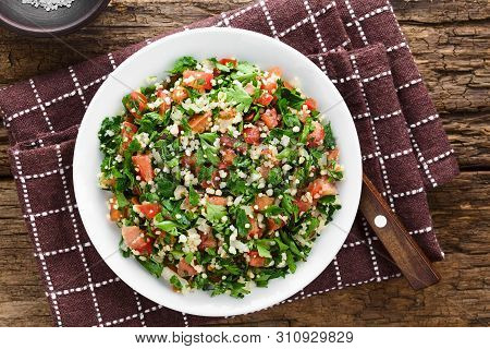 Fresh Vegan Tabbouleh Salad Made Of Tomato, Parsley, Onion And Couscous On Plate, Photographed Overh