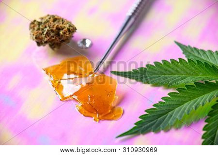 Macro detail of dab tool with cannabis concentrate aka shatter and marijuana leaf, cannabis extraction concept