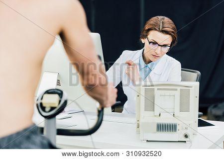 sportsman training on elliptical machine near doctor during endurance test poster