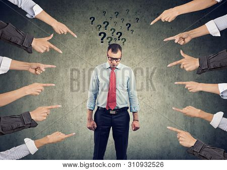 Concept Of Accusation. Sad Man With Questions Looking Down With Many Fingers Pointing At Him