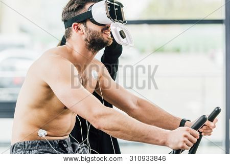 smiling shirtless sportsman in Virtual reality headset with electrodes working out on elliptical during endurance test in gym poster