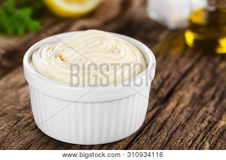 Mayonnaise Sauce In White Bowl With Parsley, Lemon, Salt And Oil In The Back (selective Focus, Focus