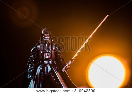 Kyiv, Ukraine - May 25, 2019: Darth Vader Figurine With Lightsaber On Black Background With Shining