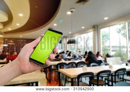 Businessman Holding Blank Screen For Text On Smartphone, Mobile, Cell Phone With Blurry Food Court B