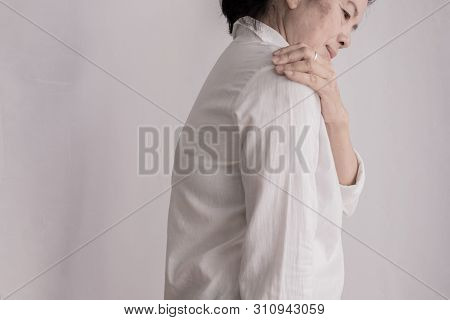 Asian Elderly Woman Having Shoulder Pain On Isolated White Background, Concept Of Healthcare.