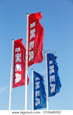 Huddinge, Sweden - July 11, 2019: A Group Of Four Ikea Flags And Flagpoles Against The Blue Clear Sk