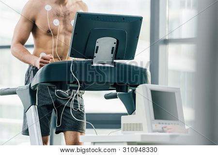 Selective Focus Of Sportsman With Electrodes Running On Treadmill During Endurance Test In Gym