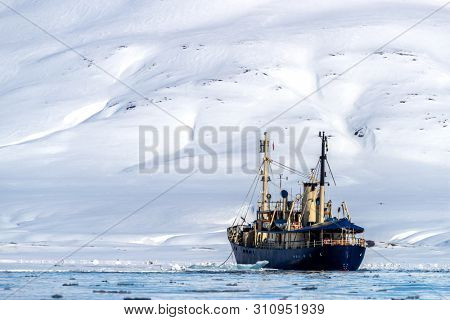 Icebreaker ship going through the fast ice of the fjords of Svalbard, a Norwegian archipelago between mainland Norway and the North Pole, with snowy mountains and blue sky.