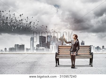 Young Woman With Smartphone Sending Text Message. Girl Sitting On Wooden Bench On Background Modern