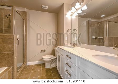 Vanity With Double Sink Adjacent To The Toilet Inside A Well Lit Bathroom