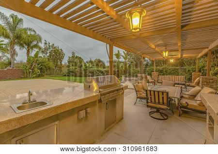 Outdoor Kitchen And Dining Area Under A Pergola At The Spacious Patio Of A Home