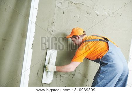 Renovation at home. Plasterer smoothing plaster on wall.