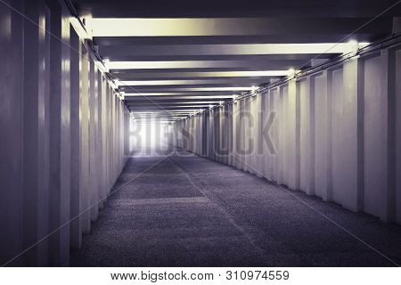 An Image Of Light At The End Of A Underground Concrete Tunnel. A Long Concrete Tunnel With Lanterns