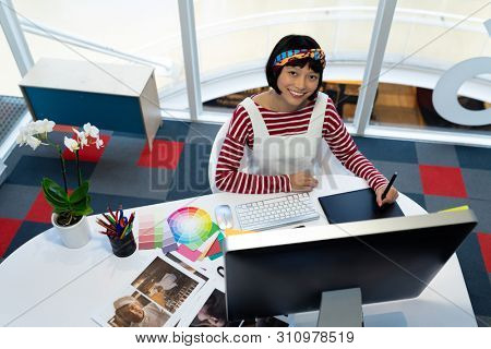 Front view of young pretty Asian female graphic designer using graphic tablet at desk in office. This is a casual creative start-up business office for a diverse team poster