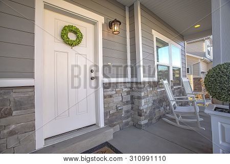Facade Of A Home With A Simple Wreath Hanging On The White Wooden Door