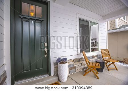 Home Facade With Glass Paned Front Door And Furniture On The Concrete Porch