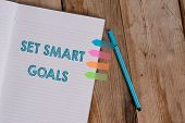 Conceptual hand writing showing Set Smart Goals. Business photo text giving criteria to guide in the setting of objectives Striped notebook colored arrow banners ballpoint wooden background. poster