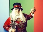 Frown senior man beefeater yeomen warder or male royal guard bodyguard in red uniform with spear on green wall poster