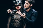 young man holding gag near sexy woman in mask and bdsm costume isolated on black poster