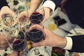 Top-down view of male and female hands with filled glasses of wine above the restaurant tabletop. Drinking toasts and clinking tumblers at a dinner party. Drinking wine at a banquet. Feast an event poster