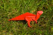 An origami dinosaur made of red paper on grass poster
