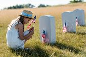sad kid in straw hat sitting near headstones and holding american flag poster
