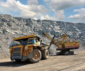 Loading of iron ore on very big dump-body truck poster