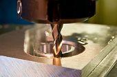 Cnc milling machine cuts a circular slot in a piece of aluminum poster