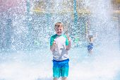 Young boy getting soaking wet while at an outdoor water park. Lots of water splashing water behind the boy. He is smiling and anticipating getting wet and drenched poster