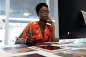 Front view of young African american female graphic designer working on graphic tablet at desk in office. This is a casual creative start-up business office for a diverse team poster