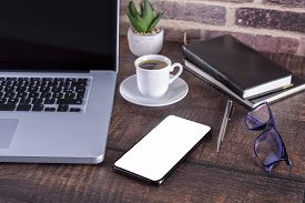 Laptop Notebook With Blank Screen And Cup Of Coffee And Notepad Pen And Book And Smartphone On Woode
