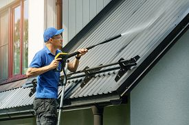 Man Standing On Ladder And Cleaning House Metal Roof With High Pressure Washer