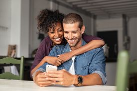 Smiling young couple embracing while looking at smartphone. Multiethnic couple sharing social media on smart phone. Smiling african girl embracing from behind her happy boyfriend while using cellphone