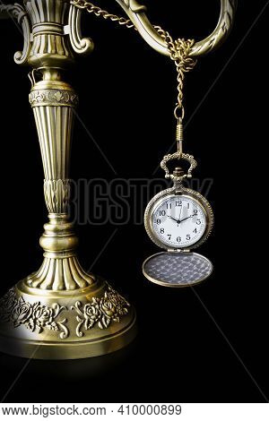 Pocket Watch Hanging On Handle Of Candlestick On Black Background. Vintage Style, Bronze.