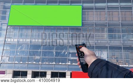 Advertising Screen On The Street Is Switched From The Remote Control. Selective Focus. Electronic Bi