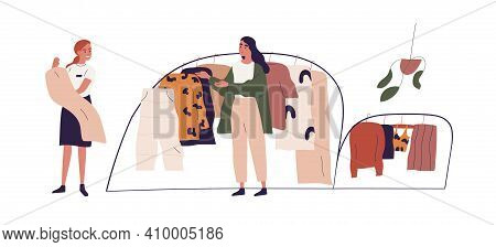 Young Woman Choosing Fashion Apparel With Help Of Shop Assistant In Clothing Store. Seller And Buyer