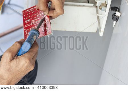 The Hands Of A Mechanic Holding A Soldering Iron And Lead To Fix The Vending Machine.