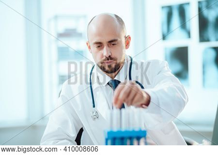 Young Scientist Looks At An Ampoule With A Vaccine.