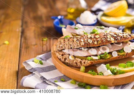 Dutch Herring In A Sandwich In Grain Bread. Toast With Dutch Herring, Onions, Pickles. Traditional R