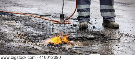 Road Worker Prepare Pothole With Gas Torch Flame For Repairing. Copy Space