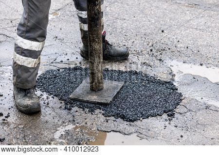 Worker Pushing Bitumen Asphalt In The Hole. Road Repair And Maintenance