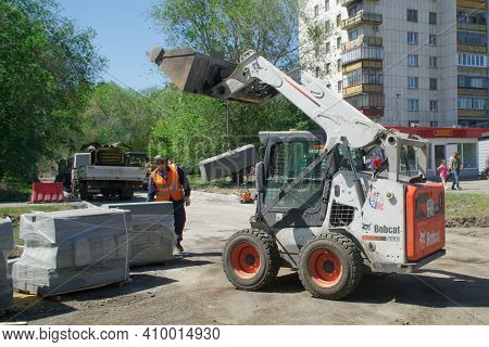 A Bobcat Skid Steer Loader Transports Construction Stone Along A City Street Next To A Worker. Insta