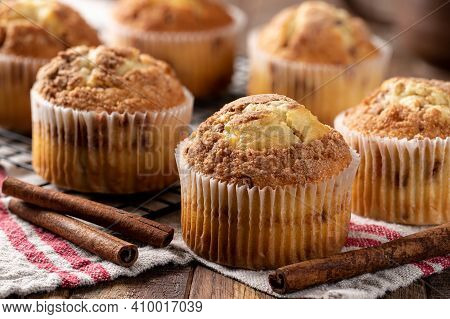 Closeup Of A Bunch Of Cinnamon Muffins And Cinnamon Sticks On A Wooden Table