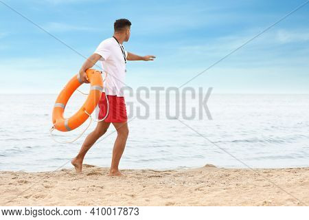 Handsome Male Lifeguard With Life Buoy At Sandy Beach