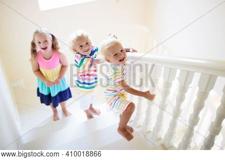 Kids Walking Stairs In White House. Children Playing In Sunny Staircase. Family Moving Into New Home