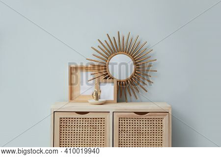 Frames And Mirror On Wooden Cabinet Near Grey Wall Indoors. Interior Design