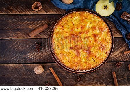 Delicious Homemade Apple Pie On Wooden Background. Apple Pie With Ingredients, Apples And Cinnamon.