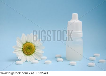 White Medical Tablets, Chamomile, White Bottle On Blue Background With Copy Space. Concept Of Allerg