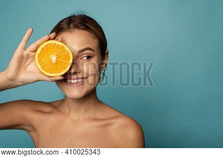 Attractive Caucasian Female With Clean Skin Laughing With Closed Eyes And Showing Half Of Fresh Oran